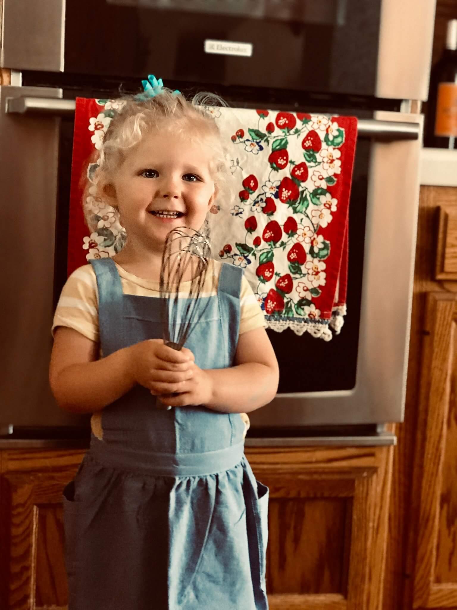 kid in kitchen holding whisk